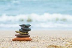 Pila de piedras de la playa en la arena Imagenes de archivo