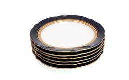 Pila de placas azules con el borde de oro Imágenes de archivo libres de regalías