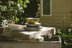 Pila de platos en un jardín dilapidado Fotos de archivo libres de regalías