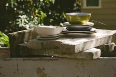 Pila de platos en un jardín dilapidado Imagenes de archivo