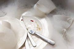 Pila de platos y de cubiertos sucios en fregadero con las burbujas Fotos de archivo libres de regalías