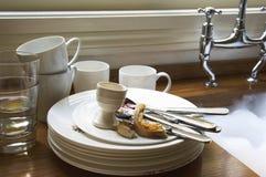 Pila de platos y de cubiertos sucios por el fregadero Imagen de archivo libre de regalías