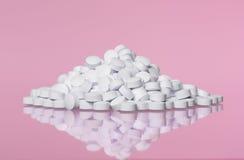 Pila de píldoras hacia fondo rosado Fotografía de archivo libre de regalías