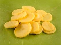 Pila de potatoe cortado en tablero plástico verde Foto de archivo