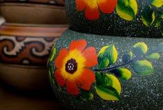 Pila de potes de cerámica mexicanos, fondo gris, flores anaranjadas Imagen de archivo