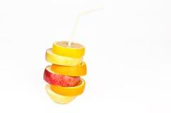 Pila de rebanadas de la naranja, del limón, de la pera y de la manzana con el jugo c de la paja imágenes de archivo libres de regalías