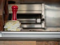 Pila de recibos empalados en un contador al lado de amoladora de pimienta roja en contador imágenes de archivo libres de regalías