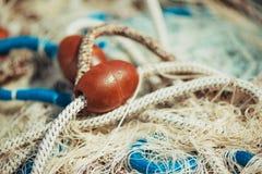 Pila de red de la pesca profesional con los cordones y los flotadores fotografía de archivo