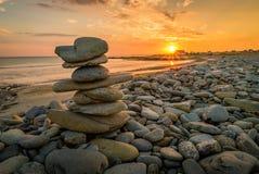 Pila de rocas núcleo de condensación en una playa en Penhors, Bretaña, Francia, en la puesta del sol foto de archivo libre de regalías
