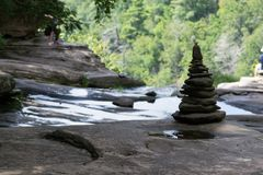 Pila de rocas por una cascada fotografía de archivo