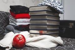 Pila de ropa y de libros del invierno con el borde brillante Imágenes de archivo libres de regalías
