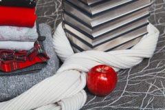 Pila de ropa y de libros del invierno con el borde de plata Fotos de archivo libres de regalías