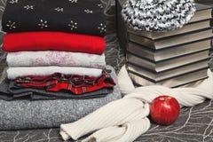 Pila de ropa y de libros del invierno con el borde de plata Imágenes de archivo libres de regalías