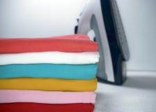 Pila de ropa y de hierro planchados en el fondo blanco imágenes de archivo libres de regalías