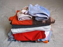 Pila de ropa y de sujetador en la cama Fotografía de archivo