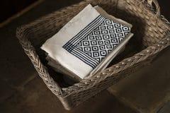 Pila de servilletas con el modelo de la casilla negra en cesta tejida imágenes de archivo libres de regalías