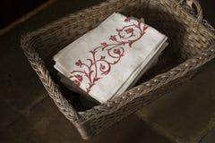 Pila de servilletas Rose-modeladas en una cesta tejida rectangular fotografía de archivo libre de regalías