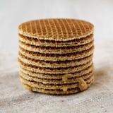 Pila de stroopwafels holandeses hechos en casa con el relleno del miel-caramelo en el paño, opinión de ángulo bajo Primer imagen de archivo