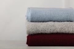Pila de suéteres hechos punto de la ropa, bufandas, azul de los jerséis, oficina imágenes de archivo libres de regalías