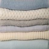 Pila de suéteres hechos punto de la ropa, bufandas, azul de los jerséis, whi foto de archivo
