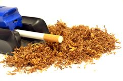Pila de tabaco y de una máquina de hacer cigarrillos foto de archivo