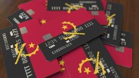 Pila de tarjetas de cr?dito con la bandera de Angola Animaci?n conceptual 3D del sistema bancario angolano almacen de metraje de vídeo