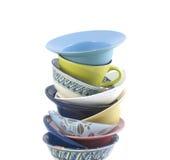 Pila de tazas coloreadas en un fondo blanco Fotografía de archivo libre de regalías