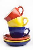 Pila de tazas coloridas en un fondo blanco Fotografía de archivo libre de regalías