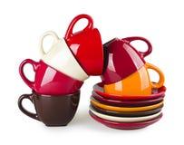 Pila de tazas y de platillos coloridos en el fondo blanco Fotografía de archivo libre de regalías