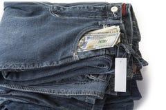 Pila de tejanos con el precio en blanco y los dólares de dinero en el bolsillo fotografía de archivo