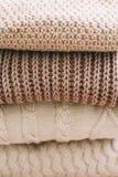 Pila de telas escocesas de lana en un fondo ligero Pila de su?teres hechos punto de la ropa, bufandas, jerse?is foto de archivo