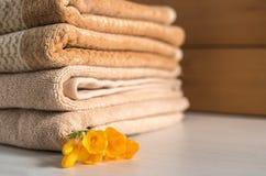 Pila de toallas beige en fondo de madera fotografía de archivo