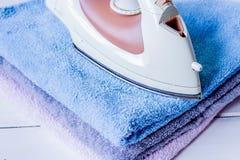 Pila de toallas coloridas con hierro en fondo de madera del lavadero fotos de archivo