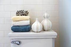 Pila de toallas con los dispensadores del jabón líquido en un cuarto de baño Fotografía de archivo