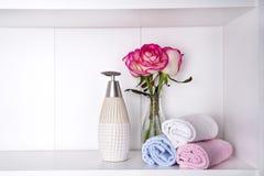 Pila de toallas con un dispensador y las rosas del jabón en vasein un primer del cuarto de baño Imagen de archivo