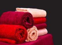 Pila de toallas de Terry coloridas en una tabla en fondo oscuro Imagenes de archivo