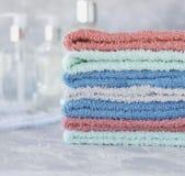 Pila de toallas para las botellas del cuarto de baño en un fondo de mármol blanco, espacio para el texto, foco selectivo Imagen de archivo libre de regalías