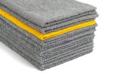 Pila de toallas de Terry grises y amarillas, aislante fotografía de archivo