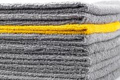Pila de toallas de Terry grises y amarillas, conceptual imagenes de archivo
