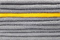 Pila de toallas de Terry grises y amarillas, fondo conceptual imagen de archivo