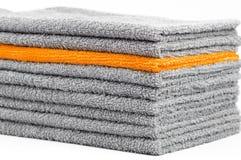 Pila de toallas de Terry grises y anaranjadas, fondo conceptual imagen de archivo