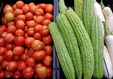 Pila de tomates rojos, de calabazas amargas verdes y de rábanos blancos en el mercado Foto de archivo