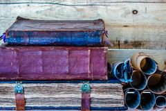 Pila de tres libros antiguos en un estante de madera fotografía de archivo