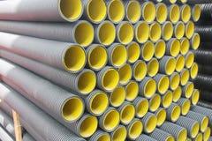 Pila de tubos plásticos acanalados amarillos negros Imagenes de archivo