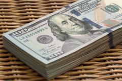 Pila de USD 100 dólares de cuentas en fondo de mimbre Imagenes de archivo