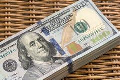 Pila de USD 100 dólares de notas sobre fondo de mimbre Foto de archivo libre de regalías
