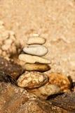 Pila del ciottolo sulla spiaggia Piramide delle pietre sulla spiaggia Luce al tramonto Simbolo di pazienza Concetto di armonia e  Fotografia Stock