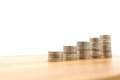 Pila del foco selectivo de dinero de las monedas en la pila de monedas aisladas en el fondo blanco foto de archivo