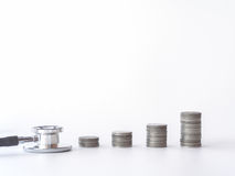 Pila della moneta e dello stetoscopio su fondo bianco soldi per la sanità, aiuto economico, concetto Fotografia Stock Libera da Diritti