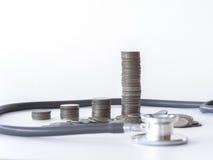 Pila della moneta e dello stetoscopio su fondo bianco soldi per la sanità, aiuto economico, concetto Fotografie Stock Libere da Diritti